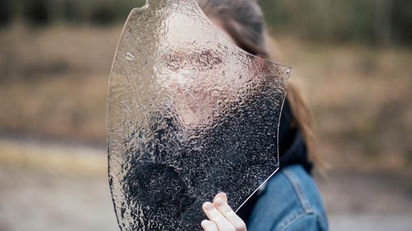 a person covering face with frosted glass